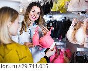 Купить «Female seller demonstrating client bras in underwear store», фото № 29711015, снято 20 марта 2017 г. (c) Яков Филимонов / Фотобанк Лори