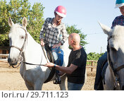 Купить «Positive mature couple with jockey learn to riding horse at farm», фото № 29711123, снято 12 декабря 2019 г. (c) Яков Филимонов / Фотобанк Лори