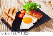 Купить «Cooked eggs with bacon, toasted bread, tomatoes and lettuce at plate on table», фото № 29711323, снято 17 января 2019 г. (c) Яков Филимонов / Фотобанк Лори