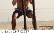 Купить «Close-up Young shirtless Muscular Man Training with Battle Ropes», видеоролик № 29712727, снято 14 сентября 2018 г. (c) Pavel Biryukov / Фотобанк Лори