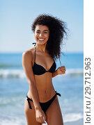 Купить «Young arabic woman with beautiful body in swimwear smiling on a tropical beach.», фото № 29712963, снято 24 сентября 2017 г. (c) Ingram Publishing / Фотобанк Лори