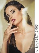 Купить «Young beautiful brunette woman in lingerie smoking cigarette», фото № 29713063, снято 28 ноября 2017 г. (c) Ingram Publishing / Фотобанк Лори