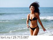 Купить «Young arabic woman with beautiful body in swimwear smiling on a tropical beach.», фото № 29713087, снято 24 сентября 2017 г. (c) Ingram Publishing / Фотобанк Лори