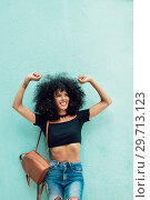 Купить «Funny black woman with afro hair raising arms outdoors», фото № 29713123, снято 23 мая 2018 г. (c) Ingram Publishing / Фотобанк Лори