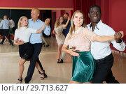 Купить «Positive adult pairs enjoying dancing salsa in modern dance studio», фото № 29713627, снято 4 октября 2018 г. (c) Яков Филимонов / Фотобанк Лори