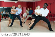 Купить «Portrait of positive adult pairs enjoying tango in modern dance hall», фото № 29713643, снято 4 октября 2018 г. (c) Яков Филимонов / Фотобанк Лори