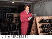 Купить «man wearing uniform working with bottle storage racks», фото № 29723811, снято 21 сентября 2016 г. (c) Яков Филимонов / Фотобанк Лори