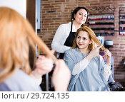 Купить «Woman points to master in hairdress salon right hair length for haircut», фото № 29724135, снято 7 марта 2017 г. (c) Яков Филимонов / Фотобанк Лори