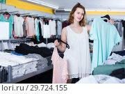 Купить «Young female customer selecting new garments», фото № 29724155, снято 19 июня 2017 г. (c) Яков Филимонов / Фотобанк Лори