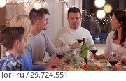 Купить «happy family having dinner party at home», видеоролик № 29724551, снято 7 января 2019 г. (c) Syda Productions / Фотобанк Лори