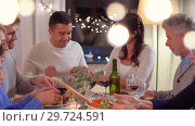 Купить «happy family having dinner party at home», видеоролик № 29724591, снято 7 января 2019 г. (c) Syda Productions / Фотобанк Лори