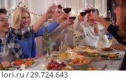 Купить «happy family having dinner party at home», видеоролик № 29724643, снято 7 января 2019 г. (c) Syda Productions / Фотобанк Лори
