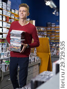 Купить «Happy guy standing with stack of DVDs in hands in shop», фото № 29729535, снято 15 февраля 2018 г. (c) Яков Филимонов / Фотобанк Лори