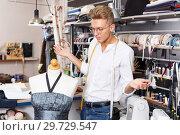 Купить «Puzzled dressmaker standing near dummy», фото № 29729547, снято 20 октября 2018 г. (c) Яков Филимонов / Фотобанк Лори