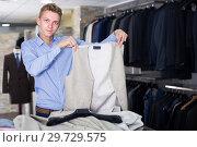 Купить «Man choosing waistcoat in the dress shop», фото № 29729575, снято 28 сентября 2017 г. (c) Яков Филимонов / Фотобанк Лори