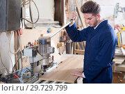 Купить «Young male carpenter adjusting chipboard», фото № 29729799, снято 7 ноября 2016 г. (c) Яков Филимонов / Фотобанк Лори