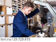 Купить «Male joiner working with trimming machine at workshop», фото № 29729815, снято 7 ноября 2016 г. (c) Яков Филимонов / Фотобанк Лори