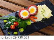 Купить «Dish scotch egg with tomatoes, mashed potatoes and greens, traditional Scottish cuisine», фото № 29730031, снято 6 июня 2020 г. (c) Яков Филимонов / Фотобанк Лори