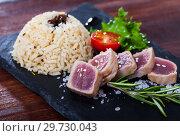 Купить «Tasty lightly fried tuna, served with rice and greens at black plate», фото № 29730043, снято 23 июля 2019 г. (c) Яков Филимонов / Фотобанк Лори