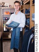Купить «Customer examining trousers», фото № 29734939, снято 28 марта 2017 г. (c) Яков Филимонов / Фотобанк Лори
