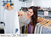 Купить «Woman choosing new long sleeve blouse», фото № 29735071, снято 26 сентября 2016 г. (c) Яков Филимонов / Фотобанк Лори