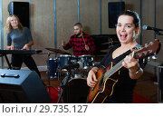 Купить «Attractive female soloist playing guitar and singing with her music band in sound studio», фото № 29735127, снято 26 октября 2018 г. (c) Яков Филимонов / Фотобанк Лори