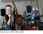 Купить «Attractive female soloist playing guitar and singing with her music band in sound studio», фото № 29735139, снято 26 октября 2018 г. (c) Яков Филимонов / Фотобанк Лори