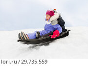 Купить «little kids sliding on sled down hill in winter», фото № 29735559, снято 10 февраля 2018 г. (c) Syda Productions / Фотобанк Лори