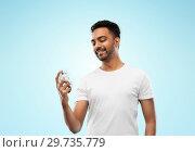 Купить «happy indian man with perfume over blue background», фото № 29735779, снято 27 октября 2018 г. (c) Syda Productions / Фотобанк Лори