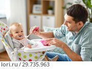 Купить «father feeding happy baby in highchair at home», фото № 29735963, снято 25 августа 2018 г. (c) Syda Productions / Фотобанк Лори