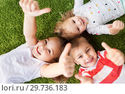 happy kids lying on floor and showing thumbs up. Стоковое фото, фотограф Syda Productions / Фотобанк Лори