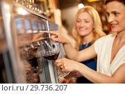 Купить «happy women pouring wine from dispenser at bar», фото № 29736207, снято 25 июня 2018 г. (c) Syda Productions / Фотобанк Лори