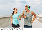 Купить «couple with headphones running outdoors», фото № 29736223, снято 1 августа 2018 г. (c) Syda Productions / Фотобанк Лори