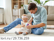 Купить «father and little baby daughter with ball at home», фото № 29736259, снято 25 августа 2018 г. (c) Syda Productions / Фотобанк Лори