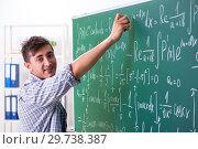 Купить «Young male student studying math at school», фото № 29738387, снято 17 октября 2018 г. (c) Elnur / Фотобанк Лори