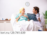 Купить «Young handsome doctor visiting female oncology patient», фото № 29741639, снято 3 октября 2018 г. (c) Elnur / Фотобанк Лори