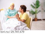 Купить «Husband looking after wife in hospital», фото № 29741679, снято 3 октября 2018 г. (c) Elnur / Фотобанк Лори