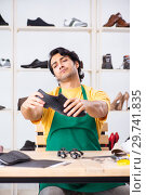 Купить «Young man repairing shoes in workshop», фото № 29741835, снято 22 октября 2018 г. (c) Elnur / Фотобанк Лори