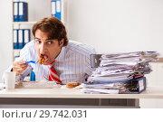 Купить «Man having meal at work during break», фото № 29742031, снято 25 сентября 2018 г. (c) Elnur / Фотобанк Лори