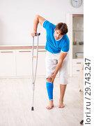 Купить «Leg injured young man with crutches at home», фото № 29743247, снято 19 сентября 2018 г. (c) Elnur / Фотобанк Лори