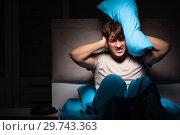 Купить «Man can not sleep due to noise neighbor», фото № 29743363, снято 18 сентября 2018 г. (c) Elnur / Фотобанк Лори