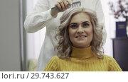 Купить «Close-up Hairdresser Makes Hairstyle For Beautiful Blonde Girl», видеоролик № 29743627, снято 20 мая 2019 г. (c) Pavel Biryukov / Фотобанк Лори