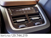 Купить «Air conditioning for passengers in the rear row of the car with a shallow depth of field. Four zone climate control. Car interior detail. Back passenger air vents.», фото № 29744219, снято 31 марта 2018 г. (c) Евгений Бобков / Фотобанк Лори
