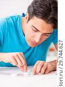 Купить «Man trying contact lenses at home», фото № 29744627, снято 6 августа 2018 г. (c) Elnur / Фотобанк Лори