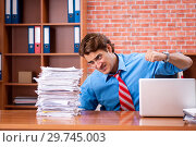 Young employee with excessive work sitting at the office. Стоковое фото, фотограф Elnur / Фотобанк Лори