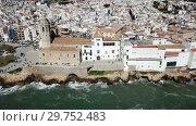 Купить «Aerial view of Sitges small town with church on Mediterranean coastline, Spain», видеоролик № 29752483, снято 27 апреля 2018 г. (c) Яков Филимонов / Фотобанк Лори