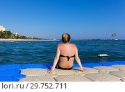 Купить «Girl sits back on the pontoon and looks at the sea and the beach in the distance», фото № 29752711, снято 17 июля 2019 г. (c) Светлана Кузнецова / Фотобанк Лори