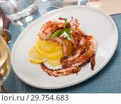 Купить «Delicious cooked squid or octopus tentacles with lemon and parsley on a plate», фото № 29754683, снято 19 марта 2019 г. (c) Яков Филимонов / Фотобанк Лори