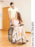 Купить «Worker brought woman in wheelchair», фото № 29754691, снято 21 января 2019 г. (c) Яков Филимонов / Фотобанк Лори