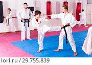 Купить «Children working in pair mastering new karate moves», фото № 29755839, снято 23 марта 2019 г. (c) Яков Филимонов / Фотобанк Лори